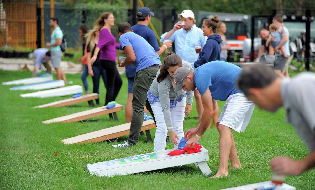 Competitors in the Corn Hole League warm up for the week of Tuesday nights competition at Mill River Park in Stamford on Sept 6, 2016. About 20 teams compete in the 7 week event sponsored by sponsored by Stamford's Half Full Brewery and Mill River Park Collaborative.