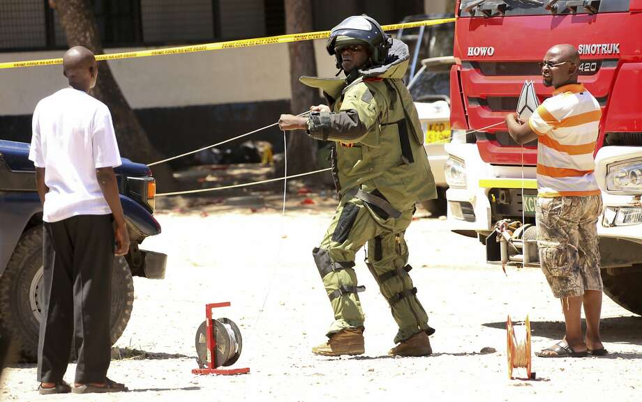 A bomb squad member examines the shooting scene outside a police station in Mombasa, Kenya Photo: STR, Associated Press