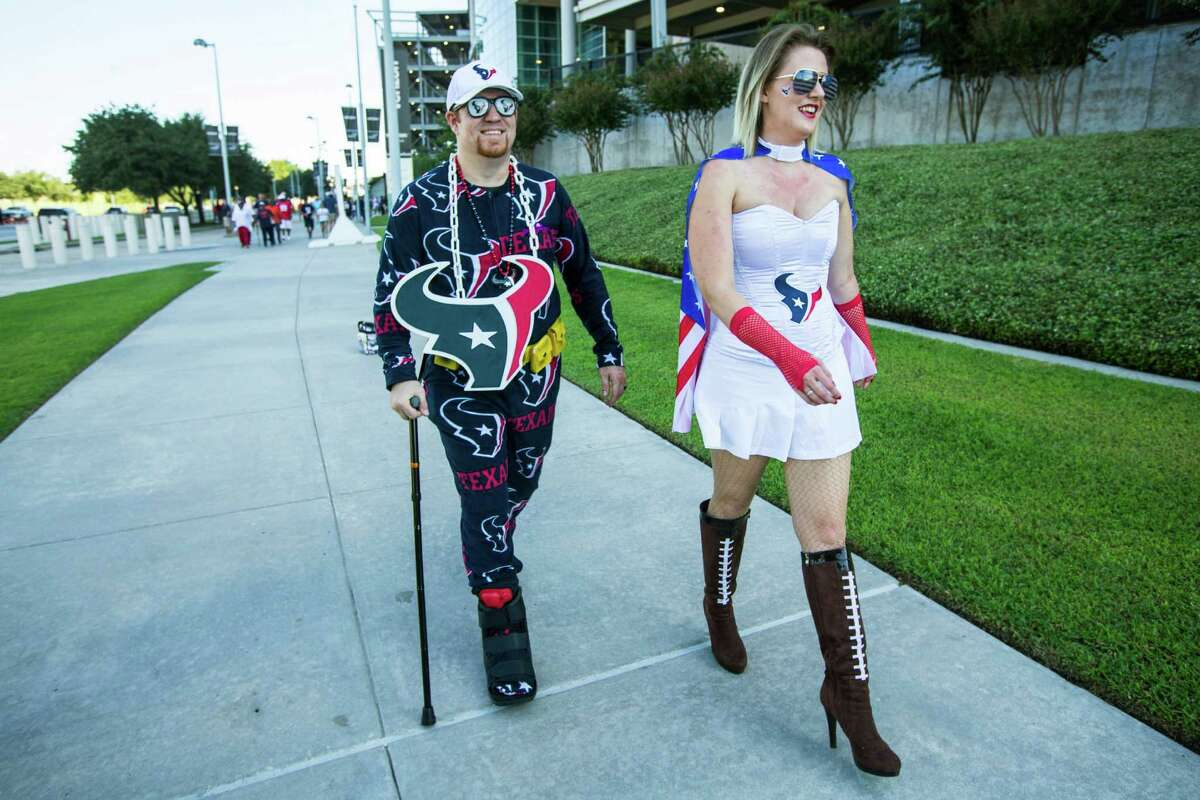 Houston Texans fans James Taylor, left, and Sarah Anderson-Taylor walk outside NRG Stadium before the NFL season opener between the Texans and Chicago Bears on Sunday, Sept. 11, 2016, in Houston.