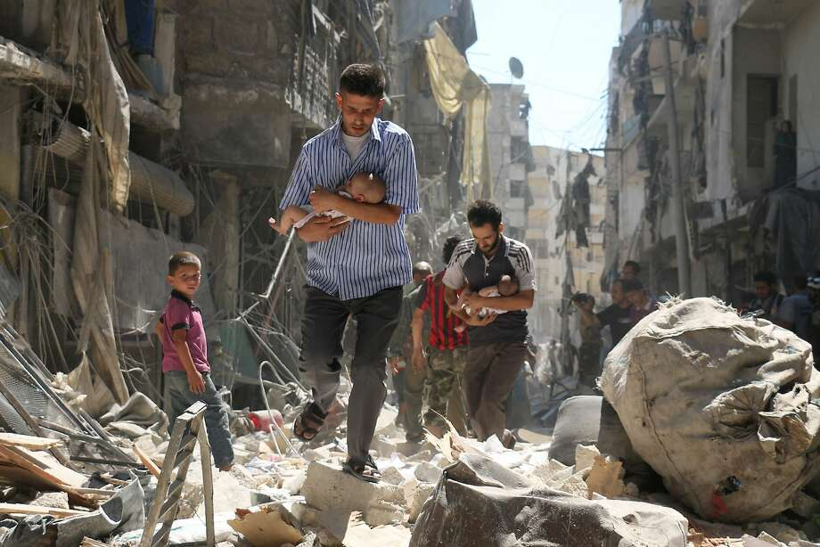 Men carry infants through the rubble of buildings destroyed in an air strike on a rebel-held neighborhood in the city of Aleppo. A cease-fire is to take effect starting Monday night. Photo: AMEER ALHALBI, AFP/Getty Images
