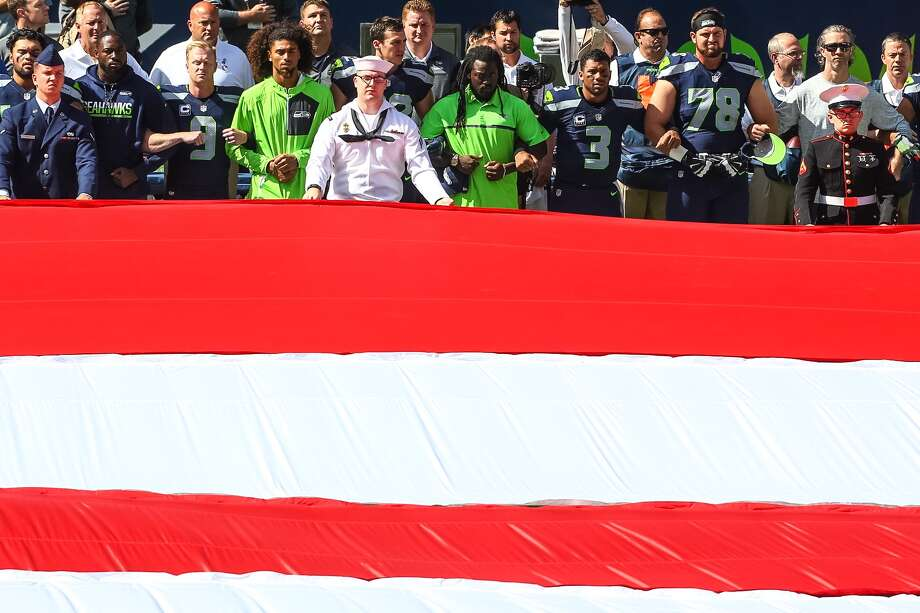 Seahawks players, including punter Jon Ryan (9), quarterback Russell Wilson (3) and tackle Bradley Sowell (78), link arms during a pregame ceremony ahead of Seattle's season-opening matchup with the Miami Dolphins on Sept. 11, 2016, at CenturyLink Field. Photo: GENNA MARTIN