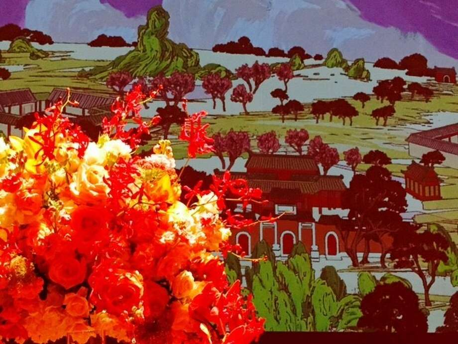 """Flowers against a projected backdrop at """"Red Chamber"""" dinner"""