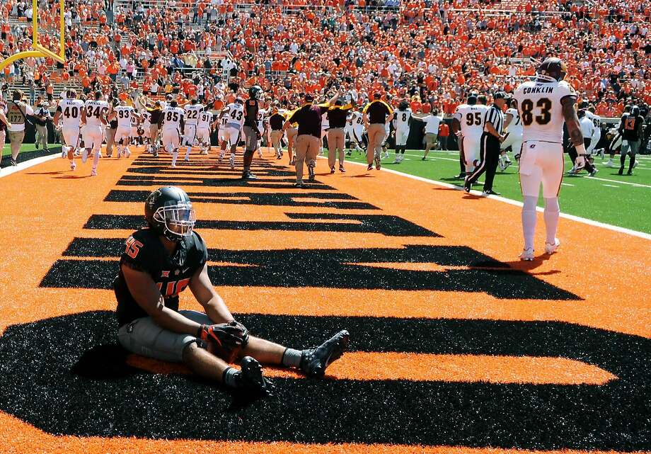 Oklahoma State linebacker Chad Whitener sits alone in the Central Michigan end zone while the Central Michigan team celebrates a last second touchdown by wide receiver Corey Willis, resulting in a 30-27 win over Oklahoma State following an NCAA college football game in Stillwater, Okla., Saturday, Sept. 10, 2016.(AP Photo/Brody Schmidt) Photo: Brody Schmidt, Associated Press
