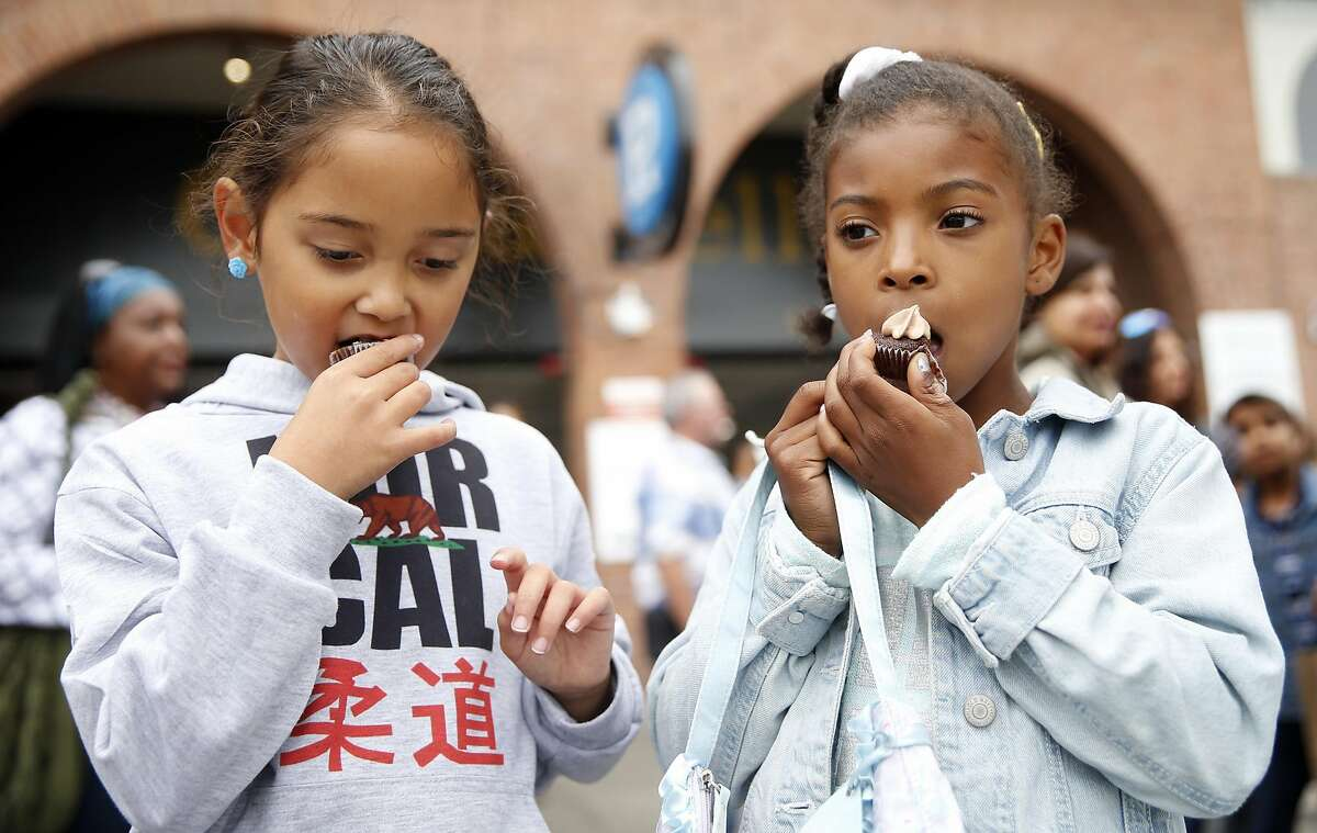 Leia Gonsalees, 8, and Toni Schaffer, 8, eat cupcakes from We the Minis booth during Ghirardelli Chocolate Festival in San Francisco, Calif., on Sunday, September 11, 2016.