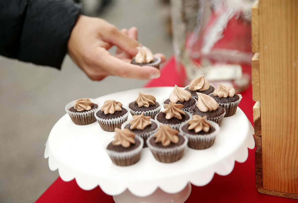 A festival goer picks up a free cupcake sample from the We the Minis booth during Ghirardelli Chocolate Festival in San Francisco, Calif., on Sunday, September 11, 2016.