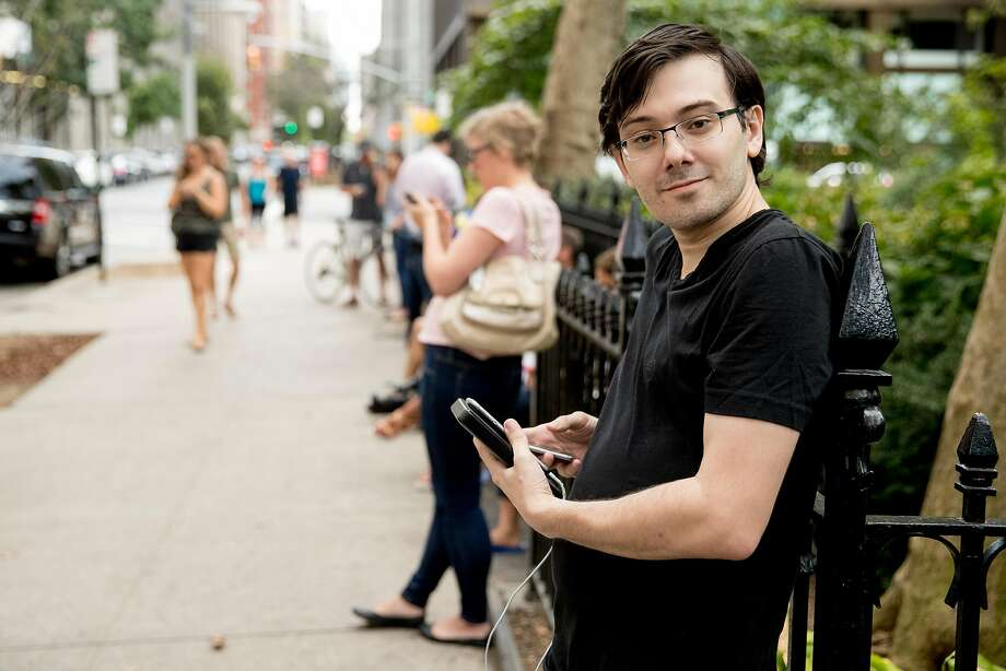 "Former Turing Pharmaceuticals CEO Martin Shkreli, who said he was reporting using a video service called ""periscope"" on his smartphone, stands with reporters after Democratic presidential candidate Hillary Clinton leaves an apartment building Sunday, Sept. 11, 2016, in New York. Following his ban from Twitter earlier this week, Shkreli will take part in a talk with Breitbart editor Milo Yiannopoulos on Friday at UC Davis. Photo: Andrew Harnik, Associated Press"