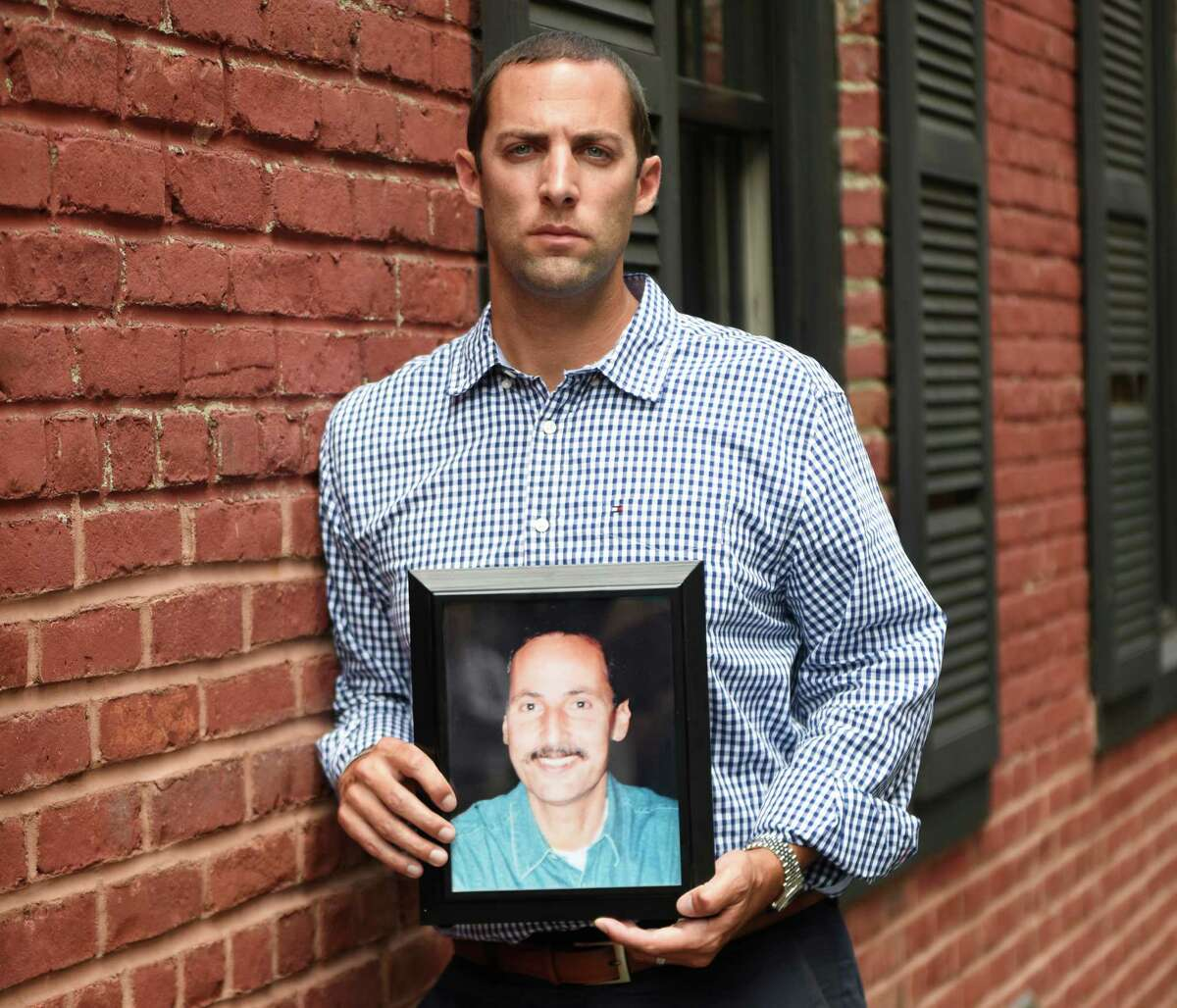 Michael Pascuma poses with a photograph of his father, also named Michael, in midtown Manhattan recently. Pascuma lost his father, a successful stock broker at the American Stock Exchange, in the World Trade Center attacks on Sept. 11, 2001. Michael graduated from Sacred Heart University in Fairfield with a double major and two minors. He now works as chief operating officer and head of business development at Solve Advisors.
