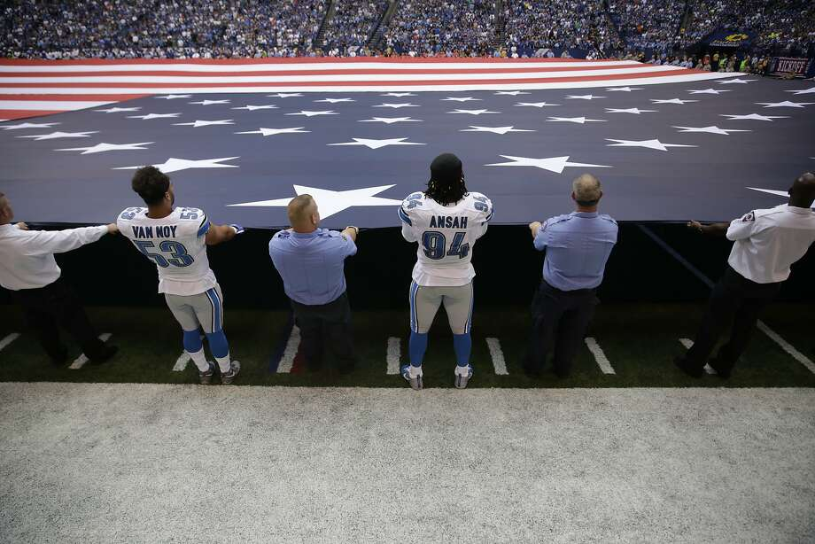 Lions players Kyle Van Noy (53) and Ezekiel Ansah (94) help first responders hold the flag in Indianapolis. Photo: Jeff Roberson, Associated Press