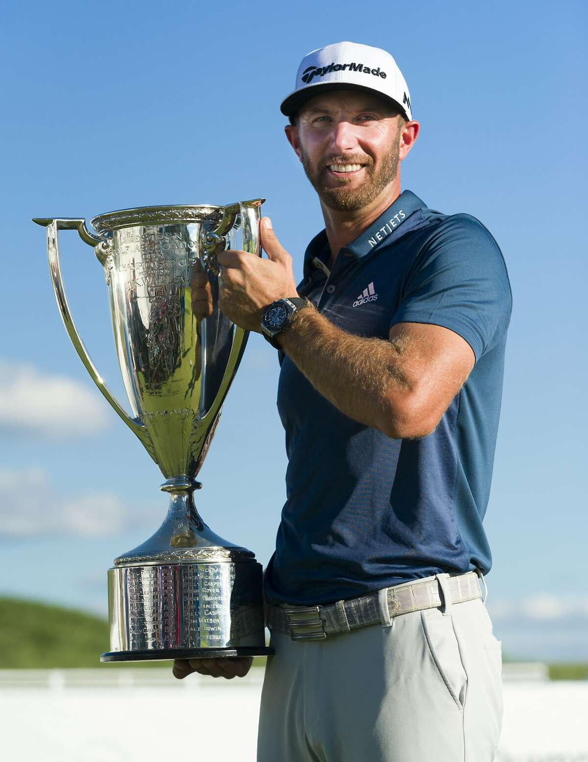 Dustin Johnson poses with his trophy after winning the BMW Championship golf tournament at Crooked Stick Golf Club in Carmel, Ind., Sunday, Sept. 11, 2016. (AP Photo/Doug McSchooler)