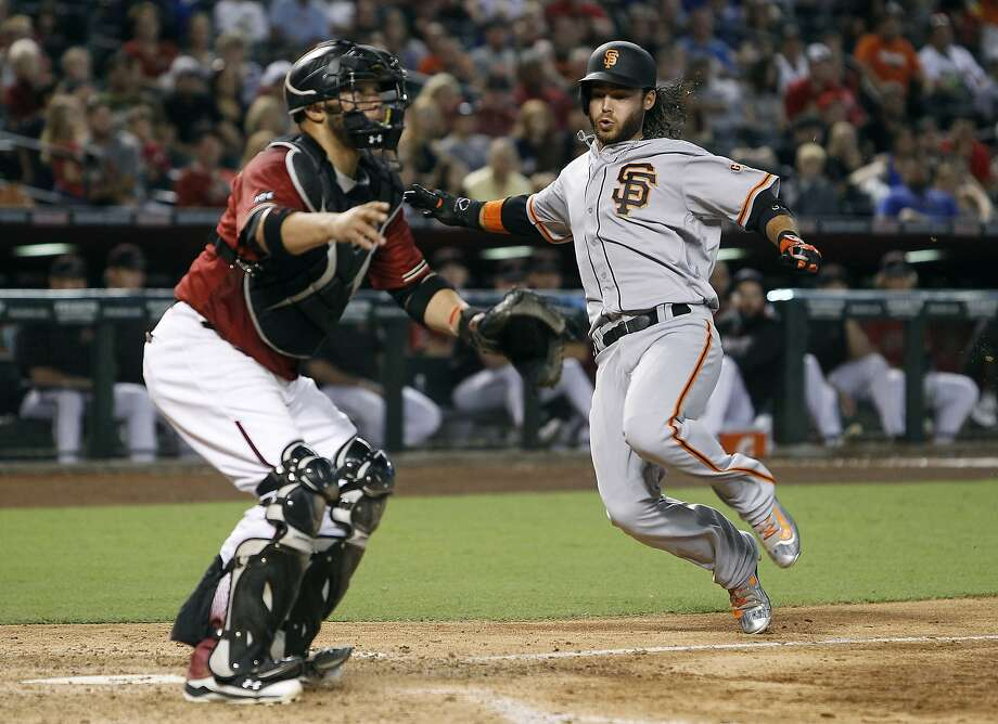 San Francisco Giants' Brandon Crawford, right, slides home to score on a double by teammate Hunter Pence as Arizona Diamondbacks catcher Weligton Castillo waits for the throw to the plate during the seventh inning of a baseball game, Sunday, Sept. 11, 2016, in Phoenix. (AP Photo/Ralph Freso) Photo: Ralph Freso, Associated Press