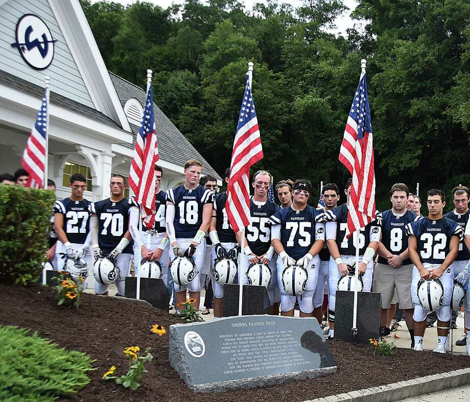 The Wilton High football team stands silently as a memorial stone for former head coach Tom Fujitani is revealed before the start of Friday's season-opening game against Fairfield Warde, which was played on Fujitani Field. Theformer coach passed away suddenly earlier this year. Photo: John Nash / Hearst Connecticut Media / Norwalk Hour