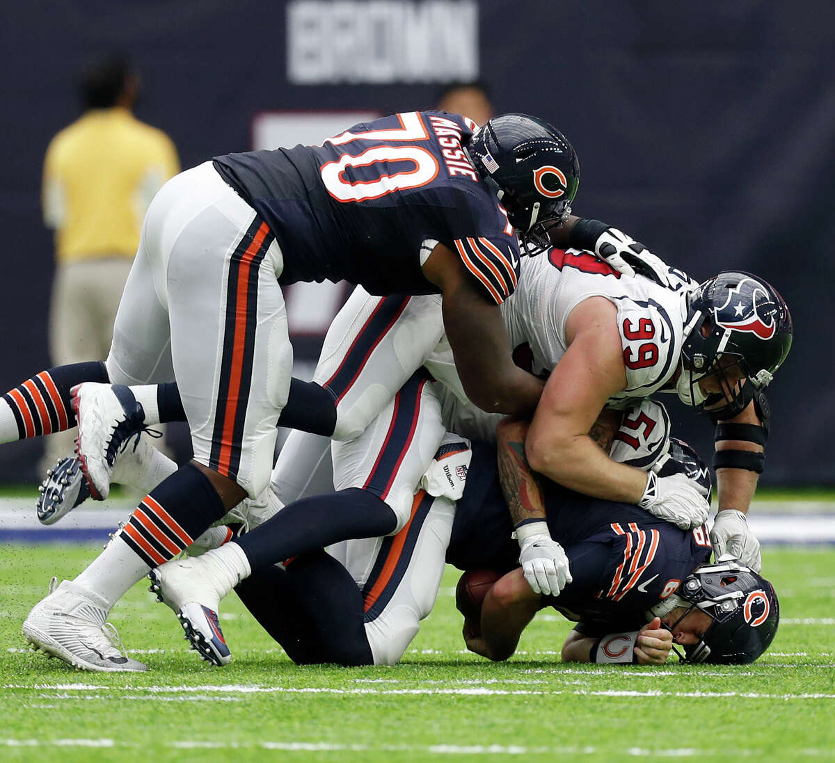 The Bears' Jay Cutler, bottom, is sacked by Texans outside linebacker John Simon (51) and defensive end J.J. Watt (99). The Texans finished with five sacks in Sunday's 23-14 victory.