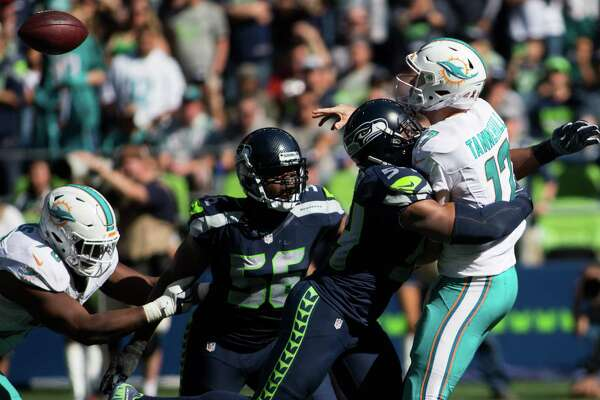 Seahawks linebacker Bobby Wagner tackles Dolphins quarterback Ryan Tannehill mid-throw in the second half of a football game at CenturyLink Field in Seattle on Sunday, Sept. 11, 2016.