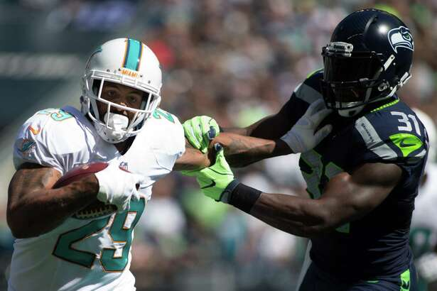 Dolphins running back Arian Foster fends off Seahawks safety Kam Chancellor in the first half of a football game at CenturyLink Field in Seattle on Sunday, Sept. 11, 2016.