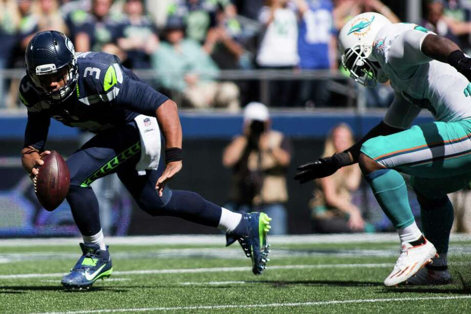 Seahawks quarterback Russell Wilson runs the ball under pressure from Dolphins defense in the first half of a football game at CenturyLink Field in Seattle on Sunday, Sept. 11, 2016. Photo: GRANT HINDSLEY, SEATTLEPI.COM / SEATTLEPI.COM