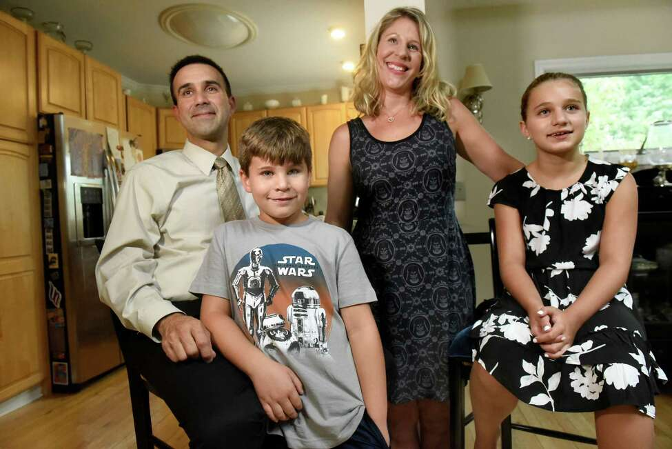 Sammy Meyers, 9, center, with his parents, Mike and Becky Meyers, and sister, Macey Meyers, 10, on Thursday, Sept. 8, 2016, at their home in Latham, N.Y. Sammy has eliminated his epileptic seizures by following a strict high-fat, low-carb diet. (Cindy Schultz / Times Union)
