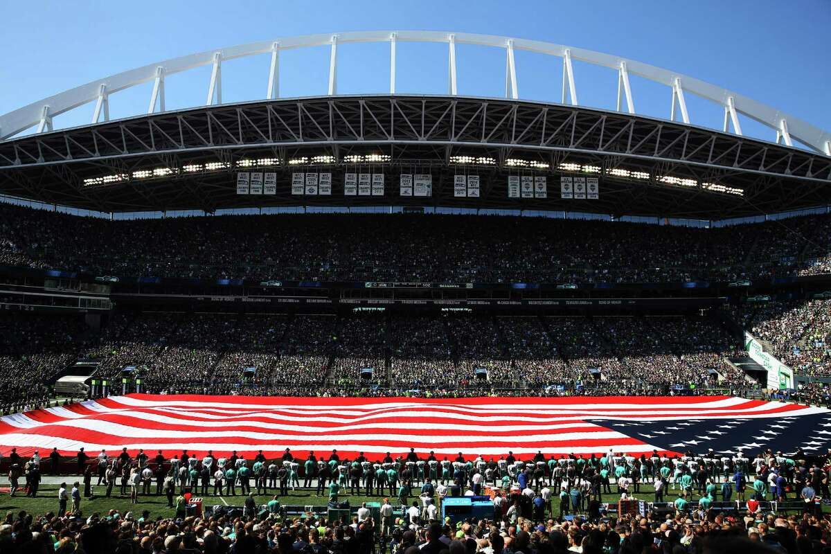 A field-sized American flag is unfurled by members of the Armed Forces before the Seahawks season opening game against Miami, Sunday, Sept. 11, 2016, at CenturyLink Field.