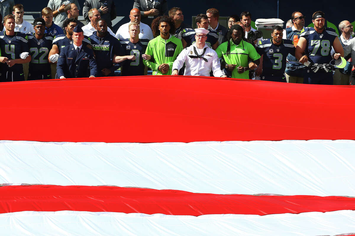 The Seahawks players link arms in a show of unity as the National Anthem is played before the Seahawks season opening game against Miami, Sunday, Sept. 11, 2016, at CenturyLink Field. Seattle won 12-10.