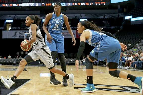 San Antonio's Moriah Jefferson (left) drives between Minnesota Lynx's Sylvia Fowles (center) and Maya Moore during first half action at the AT&T Center. Jefferson finished with 26 points.