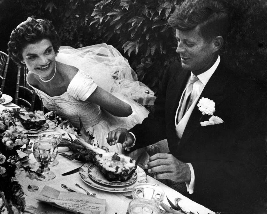 RHODE ISLAND, UNITED STATES - 1953:  Senator John Kennedy & his bride Jacqueline in their wedding attire, as they sit down together at table to begin eating a pineapple salad at formally set table outdoors at their wedding reception.  (Photo by Lisa Larsen/The LIFE Picture Collection/Getty Images) Photo: Lisa Larsen/The LIFE Picture Collection/Getty Images