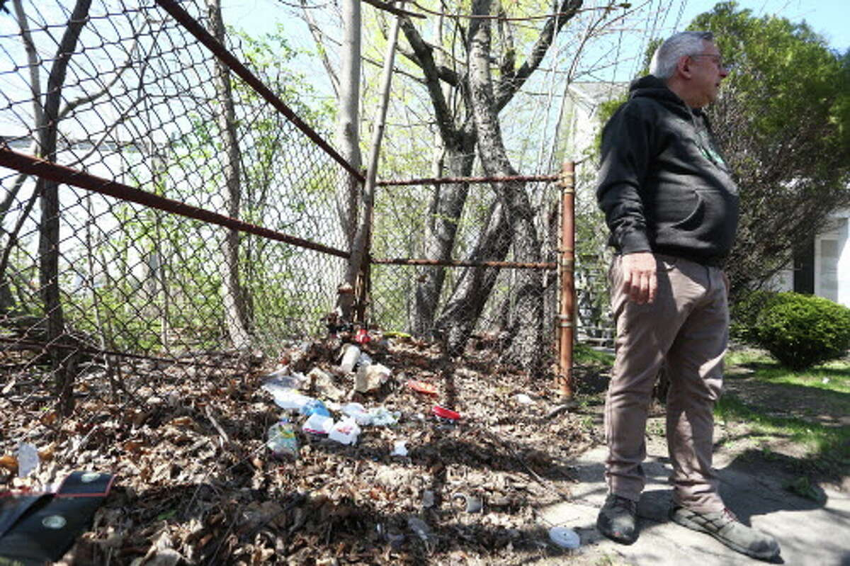 James Grunberger, chairman of the East Side Partnership, stands over a pile of trash at the end of Noroton Hill Place on Thursday, April 21, 2016. The East Side Partnership is hosting a neighborhood cleanup on Saturday which will include the removal of trash piles like this one.