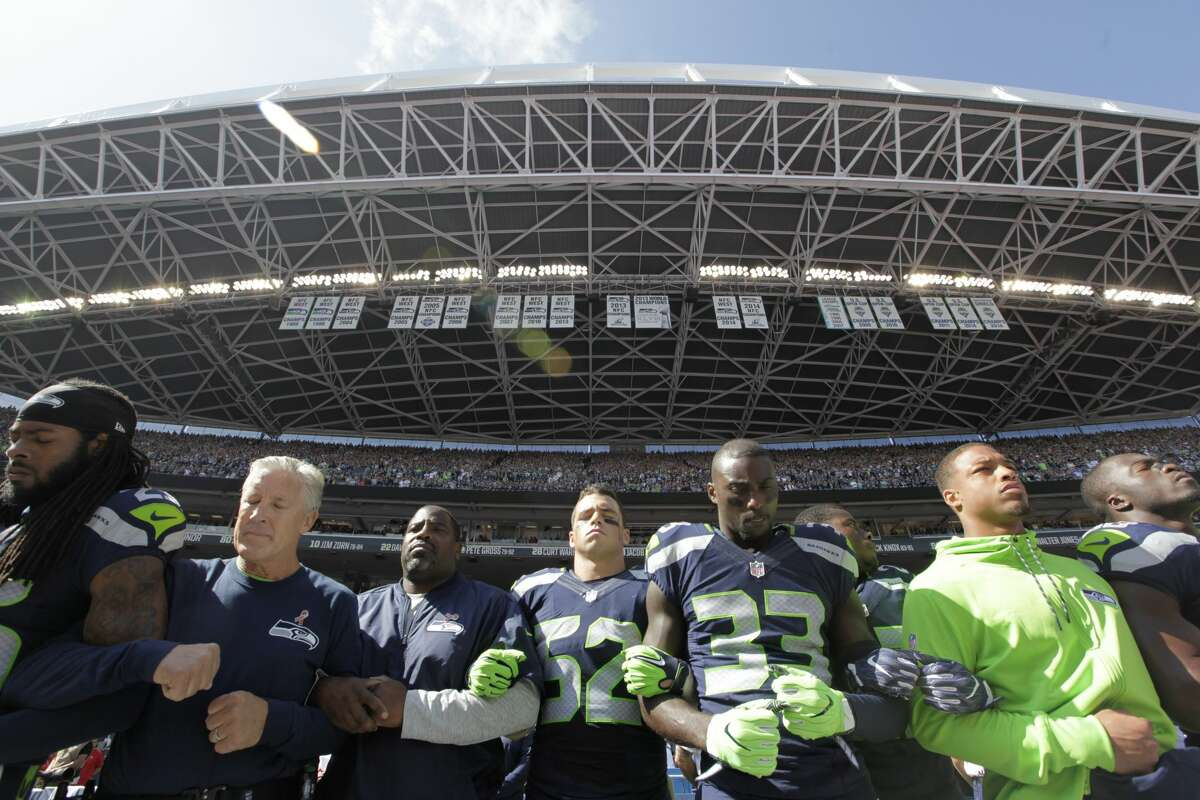Seattle Seahawks players and coaches, including cornerback Richard Sherman (25) and head coach Pete Carroll, second from left, stand and link arms during the singing of the national anthem before an NFL football game against the Miami Dolphins, Sunday, Sept. 11, 2016, in Seattle. (AP Photo/Elaine Thompson)