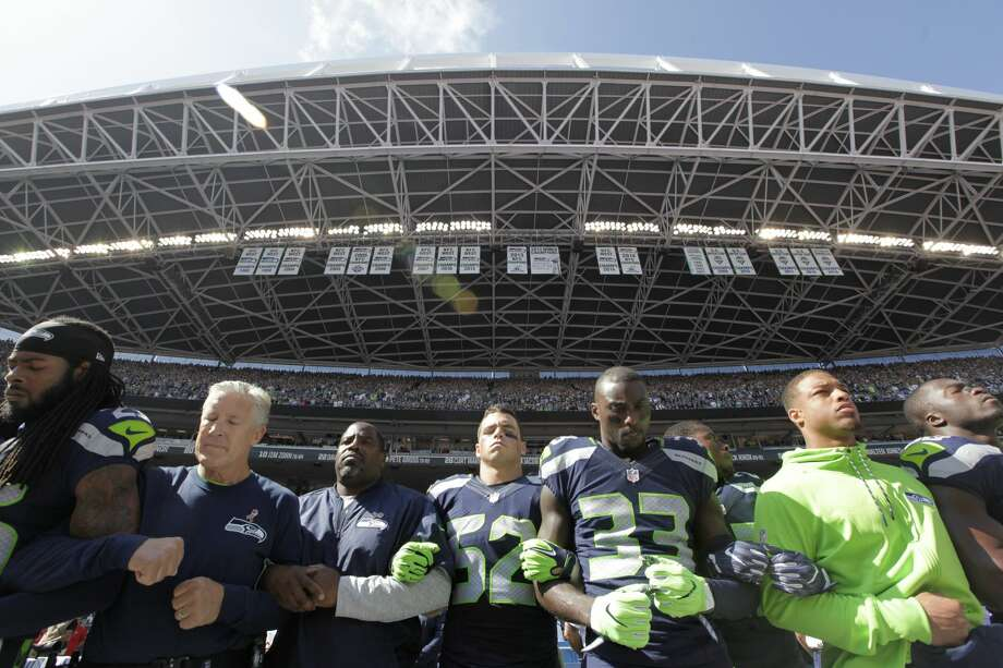 Seattle Seahawks players and coaches, including cornerback Richard Sherman (25) and head coach Pete Carroll, second from left, stand and link arms during the singing of the national anthem before an NFL football game against the Miami Dolphins, Sunday, Sept. 11, 2016, in Seattle. (AP Photo/Elaine Thompson) Photo: Elaine Thompson/AP