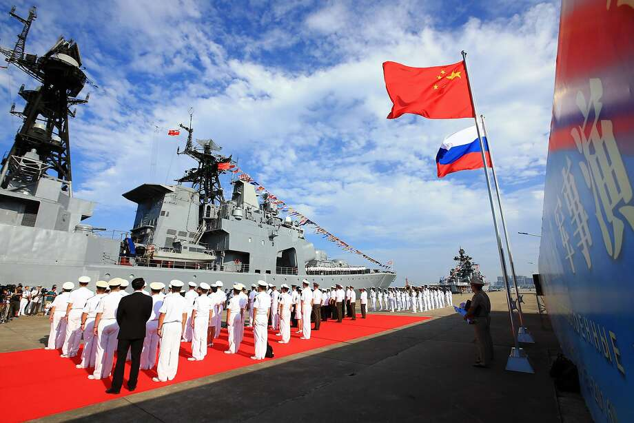 Officers and sailors of China's navy hold a welcome ceremony as a Russian warship arrives in the port of Zhanjiang in southern Guangdong Province. Photo: Zha Chunming, Associated Press