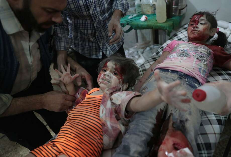 Wounded Syrian girls receive treatment at a clinic after government air strikes on the rebel-held town of Douma. A cease-fire took effect at sunset Monday. Photo: ABD DOUMANY, AFP/Getty Images