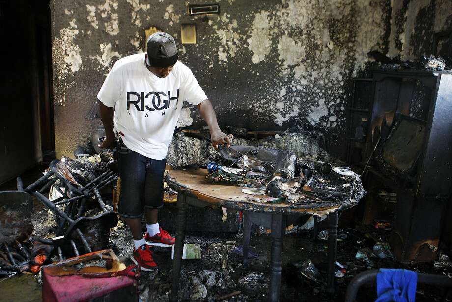 Frederick Terrell, a friend of the fire victims, looks at debris from the blaze inside the home. Photo: Karen Pulfer Focht, Associated Press