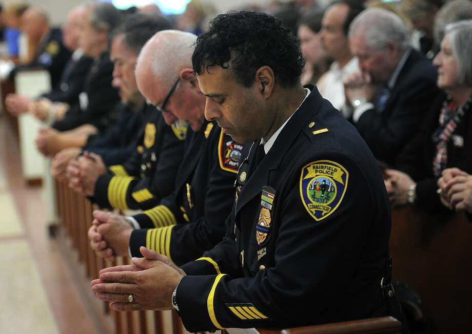 Fairfield Police Lt. James Perez, above, bows his head and prayer at the annual Diocesan Blue Mass held this year at St. Thomas Aquinas Church in Fairfield on Sunday. The Mass in honor of members of law enforcement, fire, and emergency services has been held at a different church in the diocese every year since the September 11, 2001, attacks. Photo: Brian A. Pounds / Hearst Connecticut Media / Connecticut Post