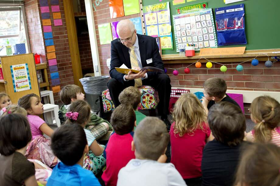 """Mauro Gregorio, CEO of Dow Corning, reads the book """"Alexander and the Terrible, Horrible, No Good, Very Bad Day"""" to Molly Kalahar's first grade class on Monday at Plymouth Elementary School. United Way of Midland County's 'Read to Succeed' classroom reading event brought volunteers from Dow Chemical, Dow Corning and Chemical Bank to first grade classrooms across Midland to read """"Alexander and the Terrible, Horrible, No Good, Very Bad Day"""" to students. Photo: NICK KING   Nking@mdn.net"""