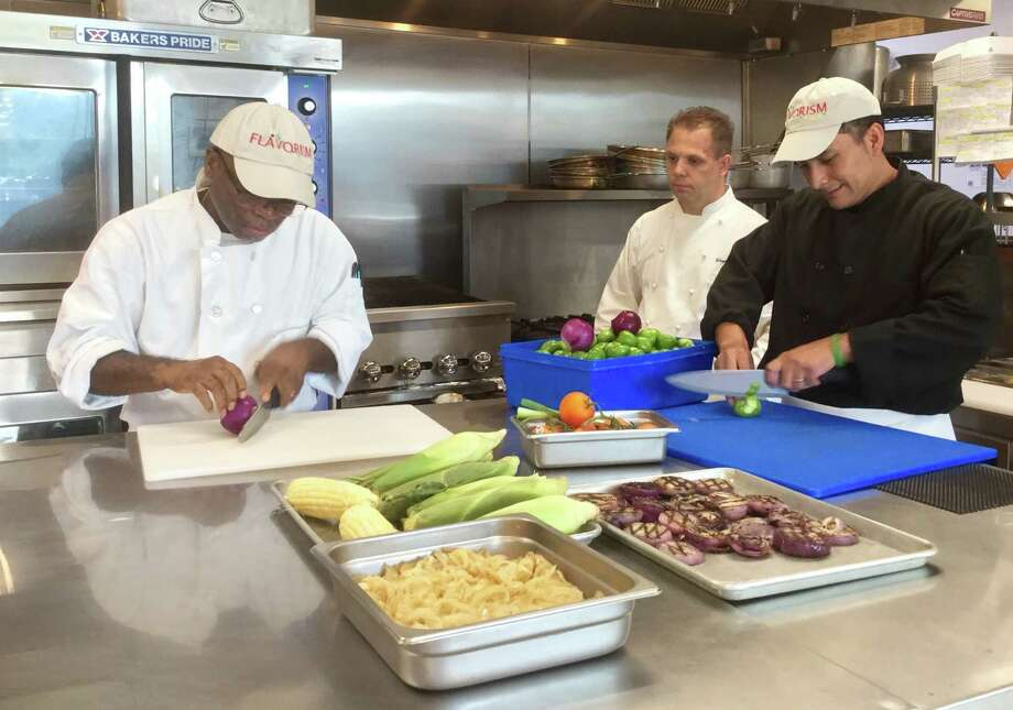 In the Flavorism culinary incubator at 207 Greenwich Ave., Puebla Grill chefs Adlin Fleurancy, left, and Plinio Lopez, right, prepare orders, while Flavorism culinary director Wayne Homsi looks on. Photo: Paul Schott /staff Photo
