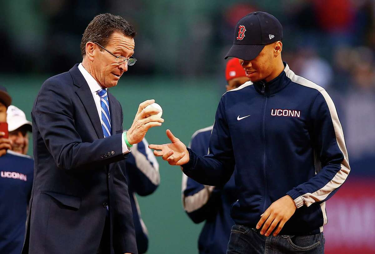 BOSTON, MA - APRIL 22: Shabazz Napier #13 and members of the national champion Connecticut Huskies basketball team wait to throw out the first pitch alongside Connecticut governor Dannel Malloy prior to the game between the Boston Red Sox and the New York Yankees at Fenway Park on April 22, 2014 in Boston, Massachusetts. (Photo by Jared Wickerham/Getty Images)
