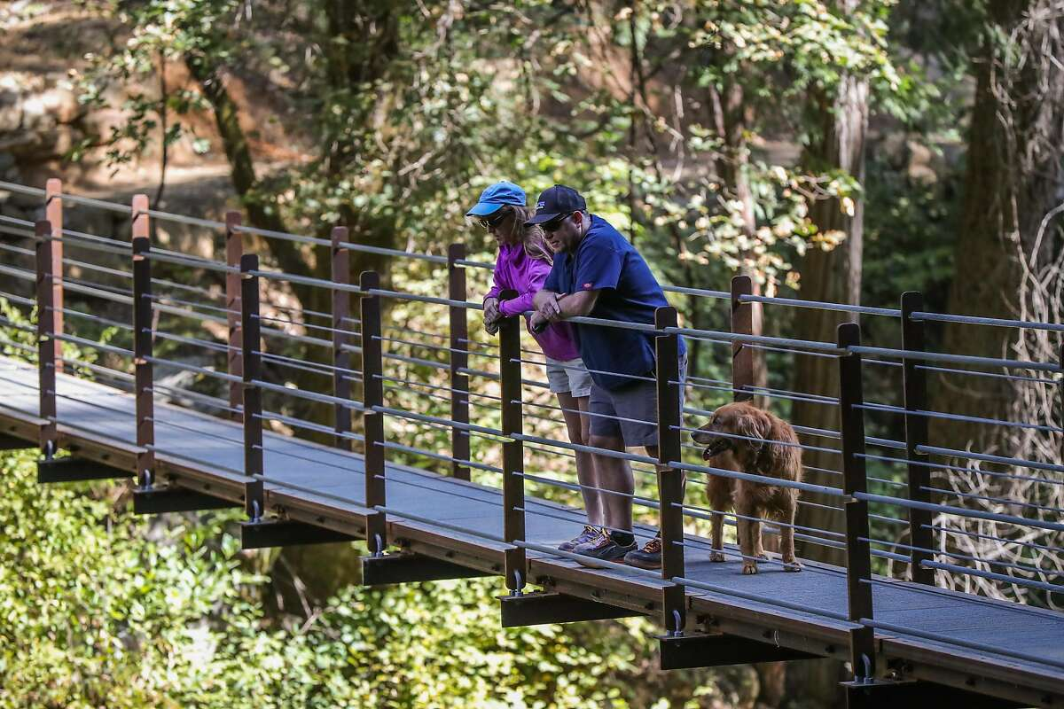 (l-r) Nancy Reese and Richard Strohl looks down at Deer Creek as they stand on a new suspension bridge, on the Deer Creek Tribute Trail in Nevada City, California, on Sunday, Sept. 4, 2016.