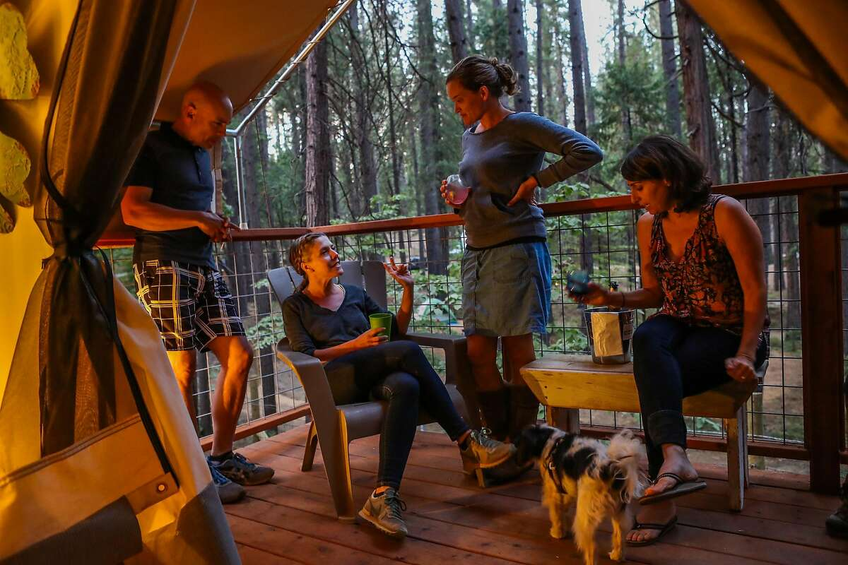 (l-r) Friends Arturo Hurtado, Kerri Hurtado, Sarah Brune and Christine Keller hang out on the porch of their glamping tent while vacationing at the Inn Town Campground in Nevada City, California, on Sunday, Sept. 4, 2016.