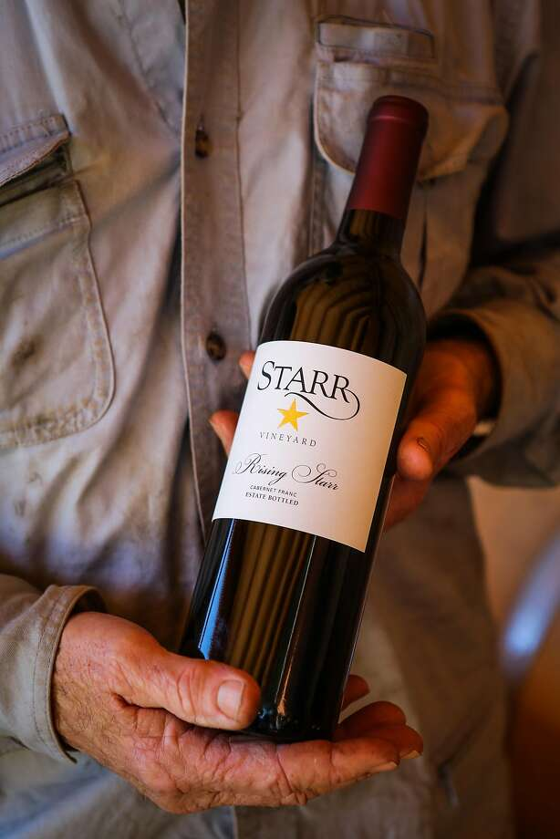 Phil Starr holds a bottle of his Cabernet Franc. Photo: Gabrielle Lurie, Special To The Chronicle