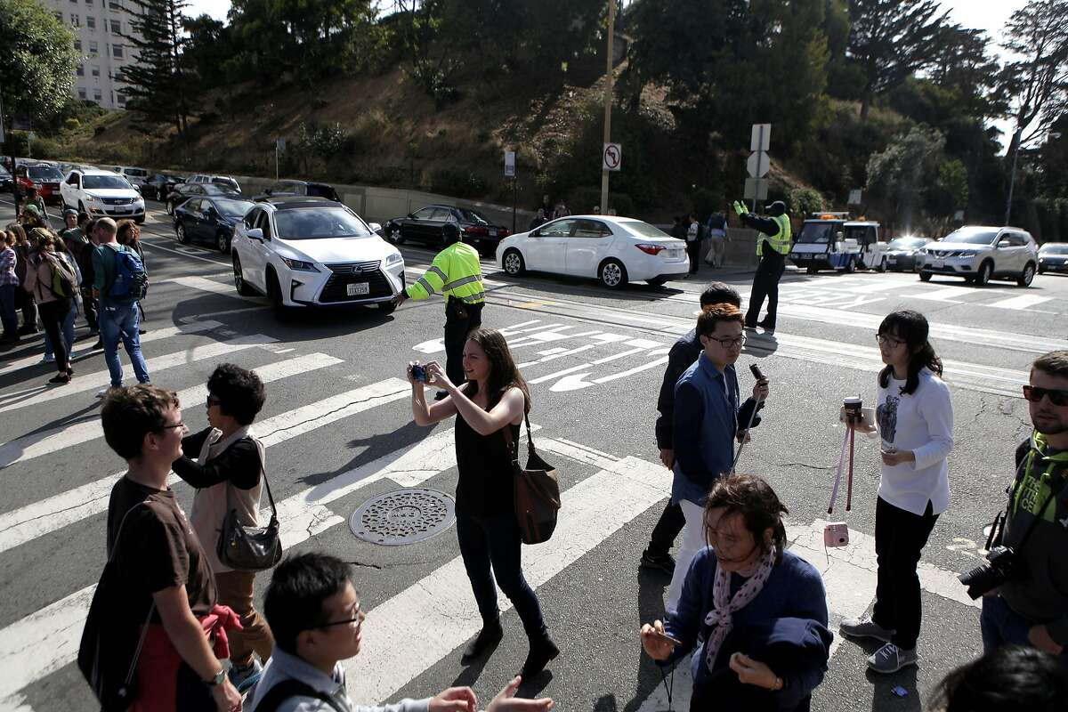A crowd of tourists block traffic from traveling down Lombard St. in San Francisco on Saturday, September 10, 2016.