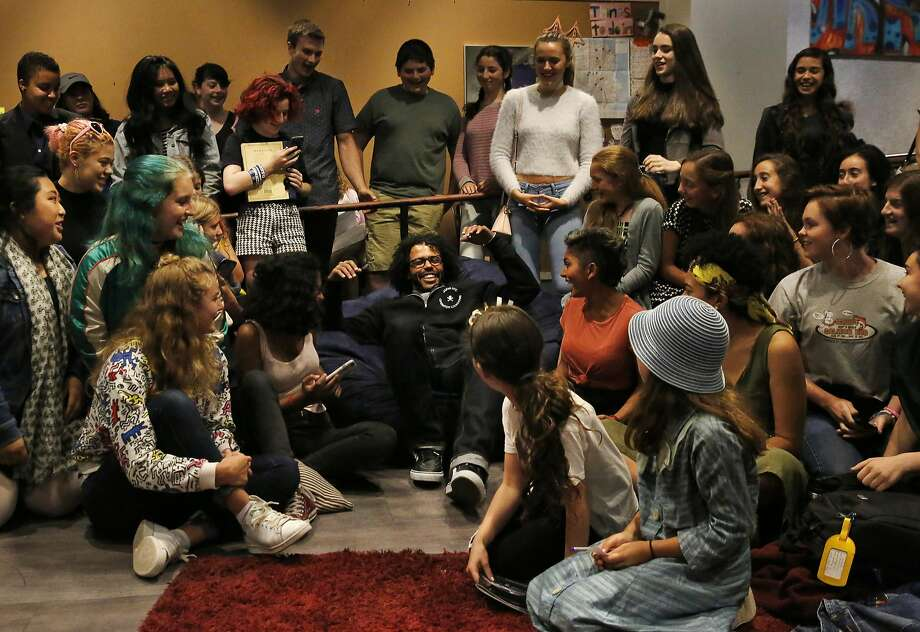 Teenagers from the teen center give an eager welcome to Daveed Diggs as he plops down in a beanbag chair. Photo: Leah Millis, The Chronicle