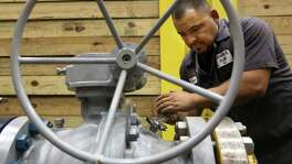 A worker tests an oil well head at Control Flow Inc. in Houston. The state's manufacturers generate nearly 15 percent of Texas' total economic output and employ more than 866,000 men and women in jobs that pay an average of nearly $80,000 a year, according to the Texas Association of Manufacturers and the Texas Association of Business. (Chronicle file photo)