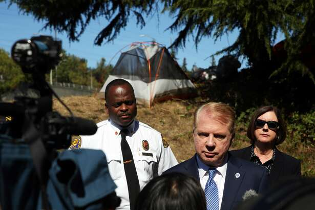 Flanked by Seattle Fire Chief Harold Scoggins, left, and Seattle Police Chief Kathleen O'Toole, right, Mayor Ed Murray speaks to the media at the site of a fatal accident that left one person dead when the car ran into a homelessness encampment near the 50th St NE Interstate 5 off-ramp in the University District, Monday, Sept. 12, 2016. (Genna Martin, seattlepi.com)