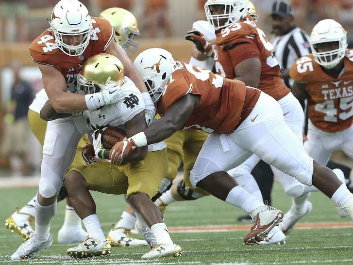 Longhorns defenders Breckyn Hager (44) and Chris Nelson get in to stop Notre Dame's Josh Admas at the line at Royal-Memorial Stadium on Sept. 4, 2016.