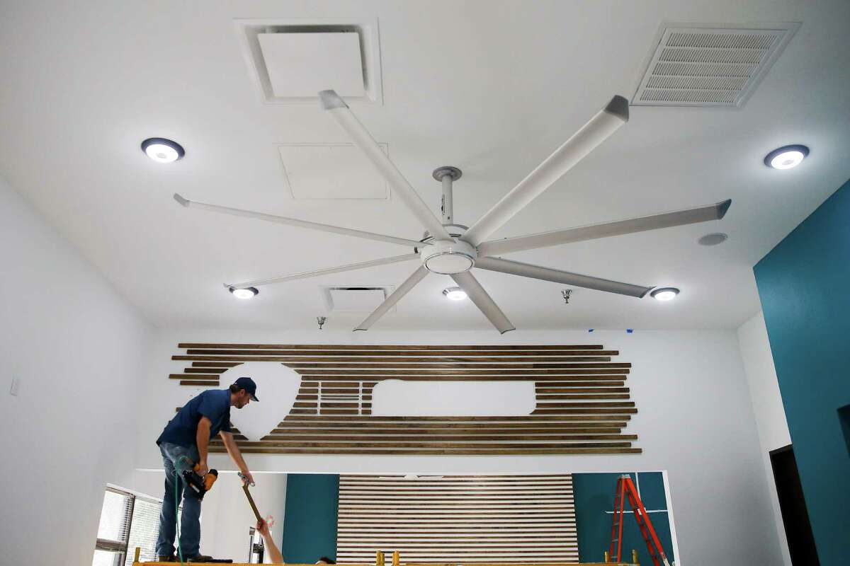 TCR Building Group project manager Jason Long hangs wood pieces for a sign as Big Ass Fans prepares to open its first showroom store Monday, September 12, 2016 in Houston. ( Michael Ciaglo / Houston Chronicle )