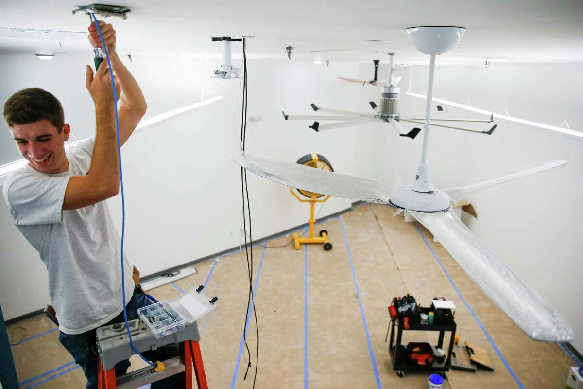 Big Ass Fans apprentice electrician Eric Delahoussaye runs wires as the company prepares to open its first showroom store Monday, September 12, 2016 in Houston. ( Michael Ciaglo / Houston Chronicle )