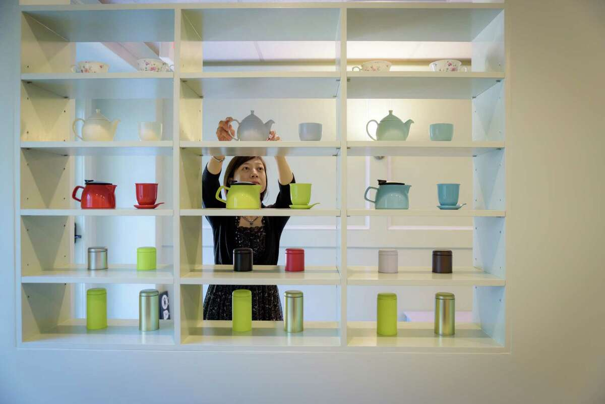 Shu-Chuan reaches for a teapot in her store, Culture Tea.