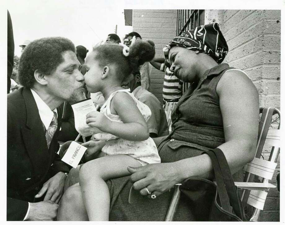 Rep. Mickey Leland gives a kiss to Annie Neal, 2, who is seated on the lap of her mother Fay, during an 18th Congressional District race campaign visit in May 1978. / Houston Chronicle