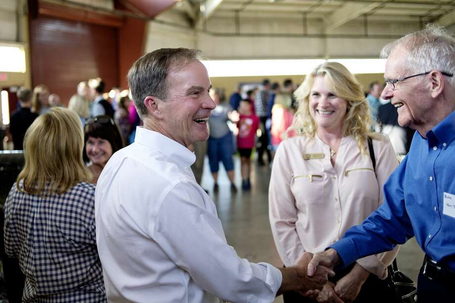 NICK KING | nking@mdn.net  Michigan Attorney General Bill Schuette, left, shakes  Bob Van Sickle's hand during Attorney General Bill Schuette's Mid-Michigan Barbeque on Monday at the Midland County Fairgrounds. Van Sickle's daughter, Midland County Treasurer Catherine Lunsford, center, looks on. Photo: Nick King/Midland Daily News