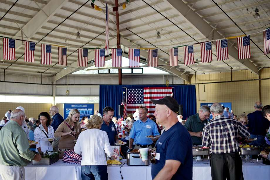 NICK KING   nking@mdn.net Guests help themselves to a buffet during Attorney General Bill Schuette's Mid-Michigan Barbeque in 2016 at the Midland County Fairgrounds. Photo: Nick King/Midland Daily News