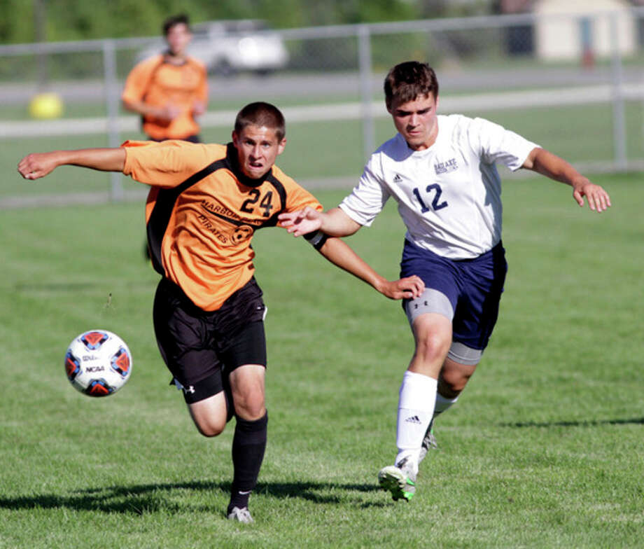 Harbor Beach's Ryan Siemen (24) and Bad Axe's Ethan Krohn (12) chase after a loose ball in the first half.