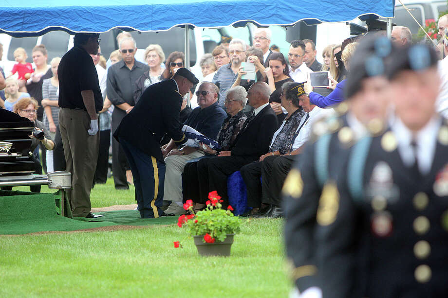 Betty Liedke of Bad Axe receives the flag that draped her brother's casket from Capt. Nicholas Graham during Saturday's funeral. Cpl. Curtis James Wells, who was killed 66 years ago in North Korea, was laid to rest after his remains were identified and returned to the United States. Seated to Liedke's right is her brother, Dale Wells. Sitting to her left is (from left) her husband, Bob Liedke, her sister-in-law, Judy Wells, and her brother, Bill Wells.